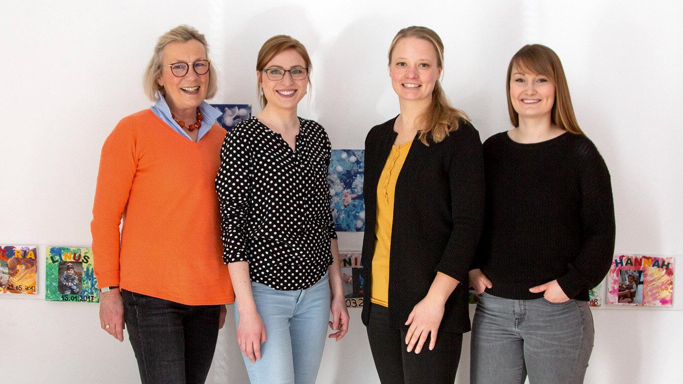 Vier Frauen stehen vor Wand